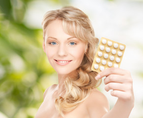 happy young woman holding package of pills