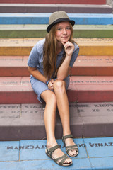 Young hipster girl sitting on colorful steps .