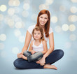 happy mother with little girl over holidays lights