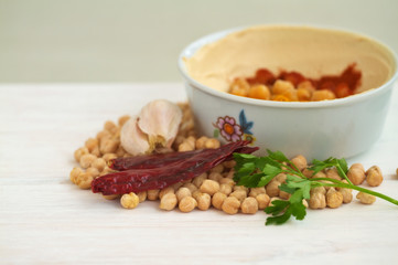 Chick peas and hummus dish on a vintage wooden background