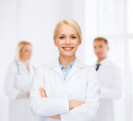 smiling female doctor with group of medics
