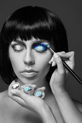 Beautiful woman applying blue eye makeup. black and white image