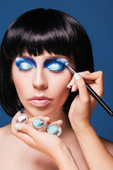 Eye makeup woman applying blue eyeshadow powder