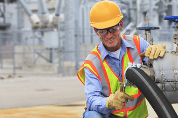 Electrical engineer inspecting hose connection at power plant