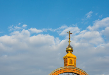 Golden Church steeple with a cross.