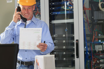 Electrical engineer looking at work order and talking on phone