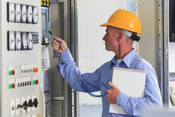 Electrical engineer inspecting controls in power plant