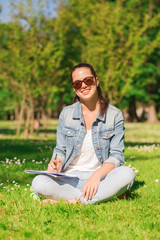 smiling young girl with notebook writing in park