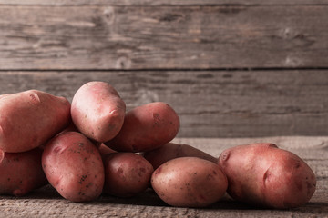 red potatoes on wooden background