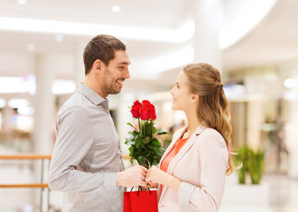 happy young couple with flowers in mall