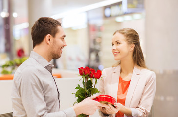happy couple with present and flowers in mall