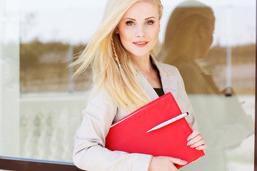 Young manager girl with a red folder and books