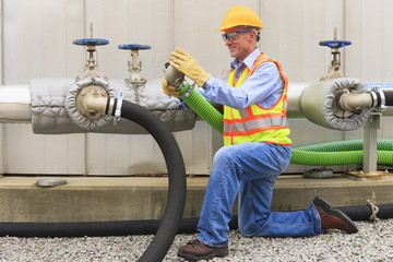 Engineer at electric power plant inspecting connection hose