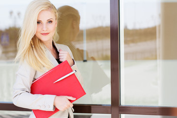 Young beautiful girl with a red folder and books