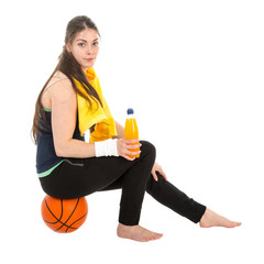Pretty woman in sports wear sitting on basketball drinking juice