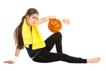Pretty woman in sports wear sitting on floor with basketball
