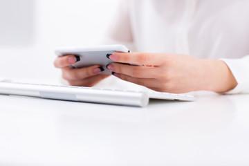 Closeup image of female hands using smartphone