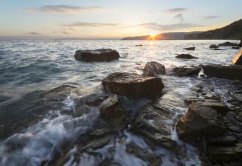 zachód słońca nad morską, skalistą plażą