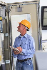 Electrical engineer inspecting power plant controls