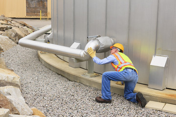 Engineer inspecting pipeline of water storage tank