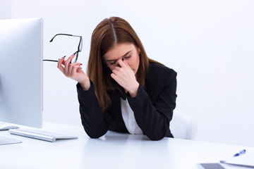 Tired businesswoman rubbing her eyes in office