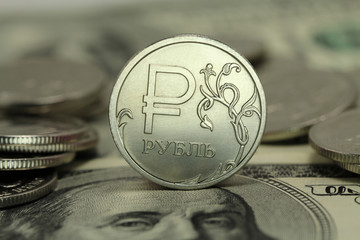 shiny coin one ruble against the background US dollars