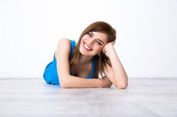Portrait of a beautiful happy woman lying on the floor