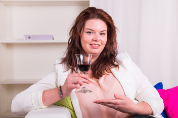 Woman on the sofa pointing a glass of wine