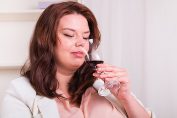 Elegant woman tests a glass of red wine