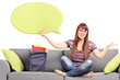 Woman holding a speech bubble seated on a sofa