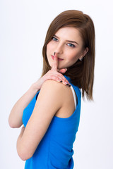Beautiful woman with secret holding finger over lips