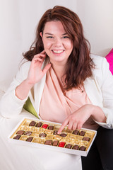 Woman eating chocolate from the box