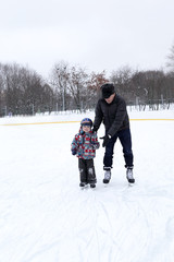 Grandfather with grandson at the skating rink