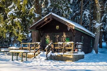 Verschneite Holzhütte im winterlichen Wald