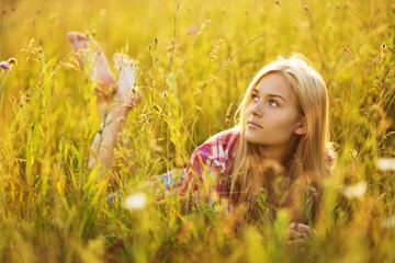 Beautiful blonde girl lying in the grass