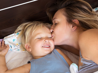 Happy mother kissing her little son.