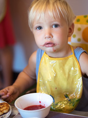 Llittle cute boy with blue eyes eating sweet jam