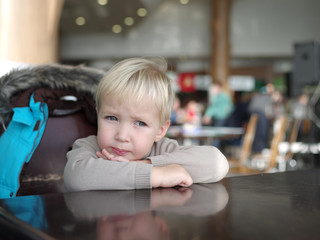 little thoughtful boy sits at a table resting his chin on his fo