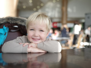 Portrait of a smiling little boy sits at a table