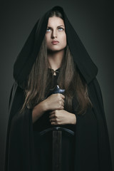 Beautiful woman with black cloak and sword