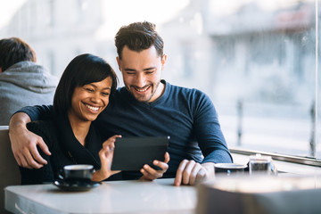 Interracial couple using tablet computer in coffee shop