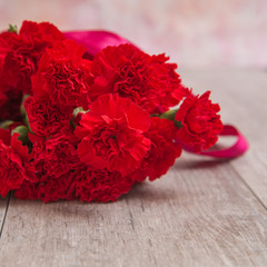 Bouquet of red carnations on wooden background