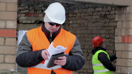 Worker with tablet PC and documentation near  building