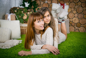 Mother and daughter hugging, winter evening together at home