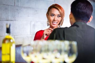 Asian couple drinking white wine in fancy bar