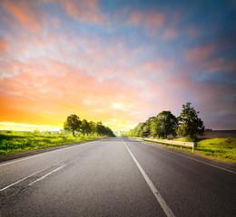 Landscape with asphalt road among fields