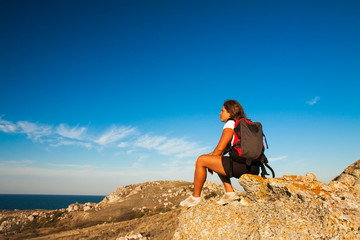 woman hiker sits on seaside mountain rock