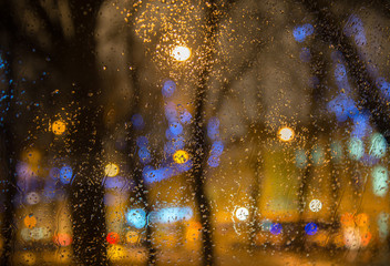 Wet  car window with the background of the night city lights