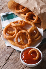 Fried onion rings and ketchup closeup. vertical top view