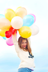 Beautiful smiling young trendy girl with bunch colored balloons